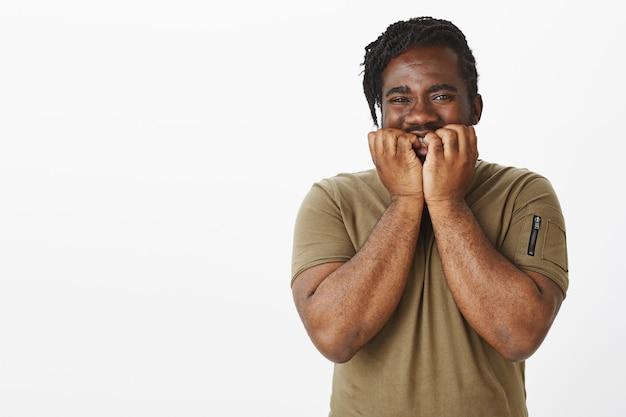 Ongeduldige man in een bruin t-shirt poseren tegen de witte muur