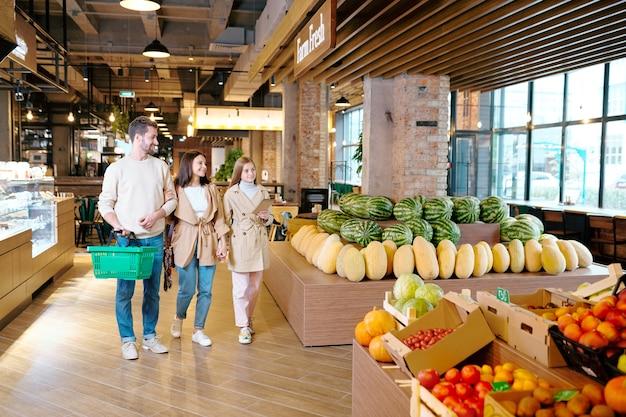 Ongedwongen jong gezin van drie die door een grote moderne supermarkt gaan terwijl ze langs vers fruit lopen
