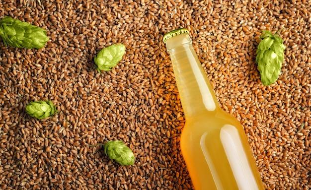 Ongefilterde bierfles op achtergrond met tarwe en weinig hop tempate klaar voor uw ontwerp