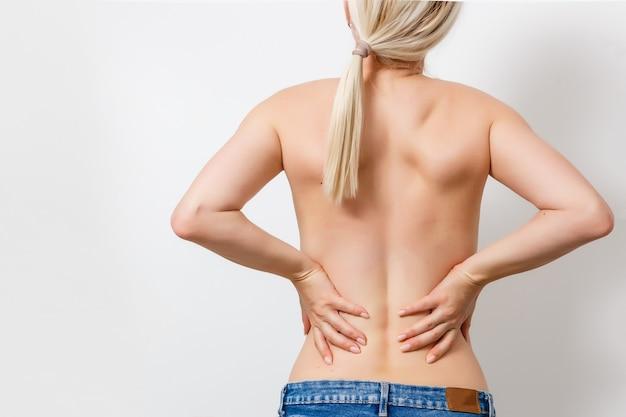 Ongeklede vrouw met rugpijn van achteren.