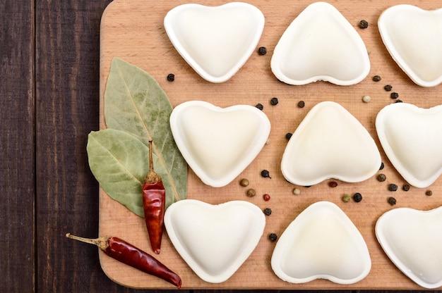 Ongekookt deeg in de vorm van een hart (dumplings, ravioli, pelmeni)