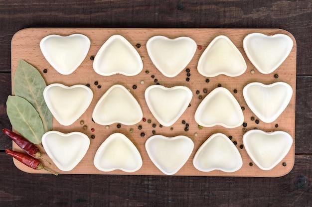 Ongekookt deeg in de vorm van een hart, op een snijplank. het bovenaanzicht