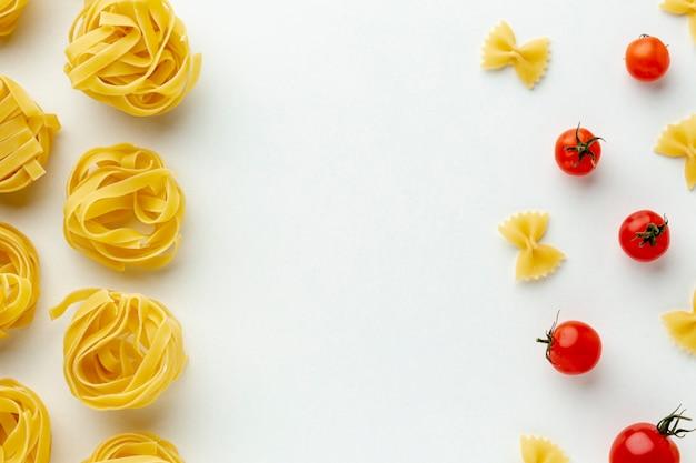 Ongekookt farfalle en tagliatelle arrangement met tomaten