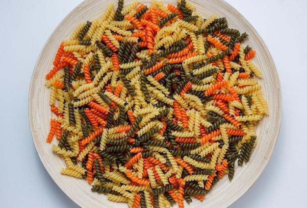 Ongekookt fusilli pasta in een plaat op witte tafel, bovenaanzicht.