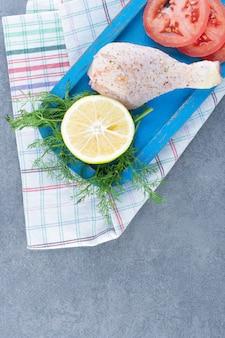 Ongekookt kippenbeen, tomaat en citroenplak op blauw bord.