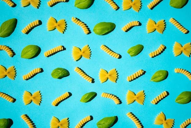 Ongekookt krullend deegwaren en basilicumbladpatroon op blauwe oppervlakte.
