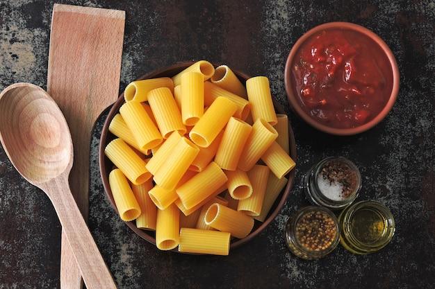 Ongekookt rigatoni pasta in een kom. tomatensaus en kruiden. houten spatel en lepel. concept koken pasta met tomatensaus. bovenaanzicht. plat leggen.