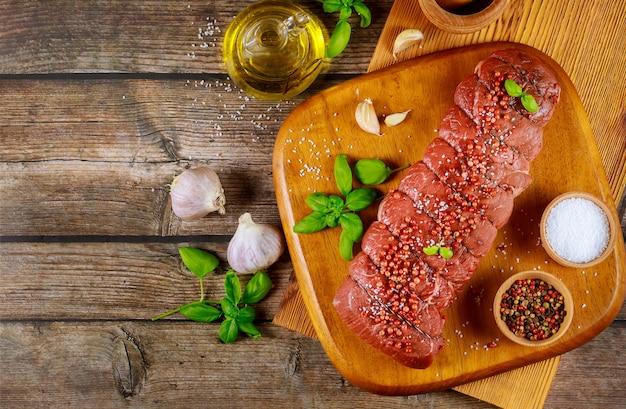 Ongekookt rundvleeslapjes vlees met kruiden en olie op houten raad.