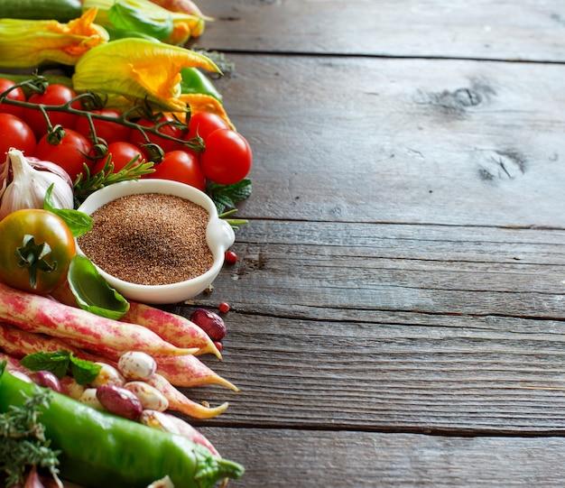 Ongekookt teffkorrel met groenten op hout