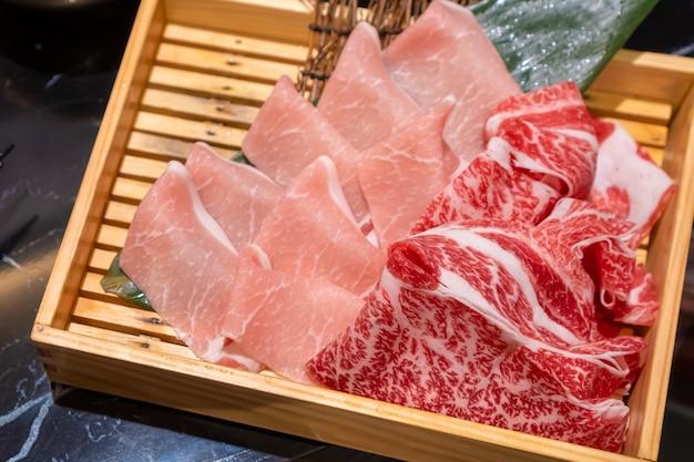 Ongekookt vers gesneden varkensvlees en rundvlees in een houten vierkante doos die voorbereidingen treft voor shabu