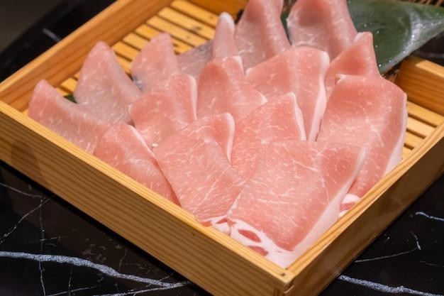 Ongekookt vers gesneden varkensvlees in een houten vierkante doos die voorbereidingen treft voor shabu