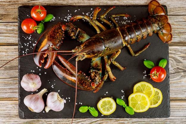 Ongekookt verse kreeft op zwarte bord met kruiden en groenten