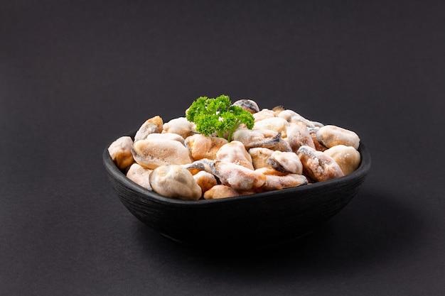 Ongekookt zeemosselenvlees met groene peterselie in een zwarte kleischotel op een donkere achtergrond.