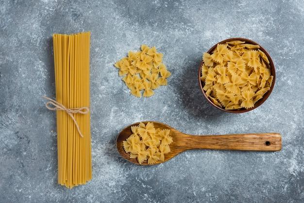 Ongekookte boogmacaroni en deegwaren met een houten lepel.