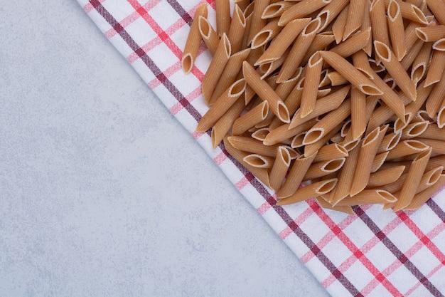 Ongekookte bruine pennedeegwaren op gestreept tafelkleed