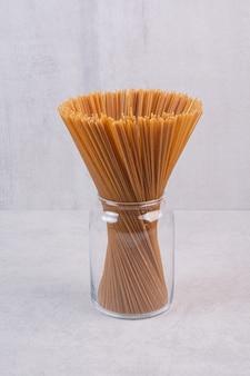 Ongekookte bruine spaghetti in glazen pot