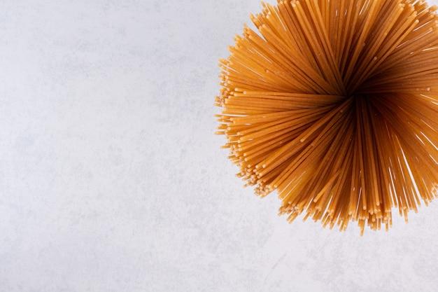 Ongekookte bruine spaghetti op stenen oppervlak