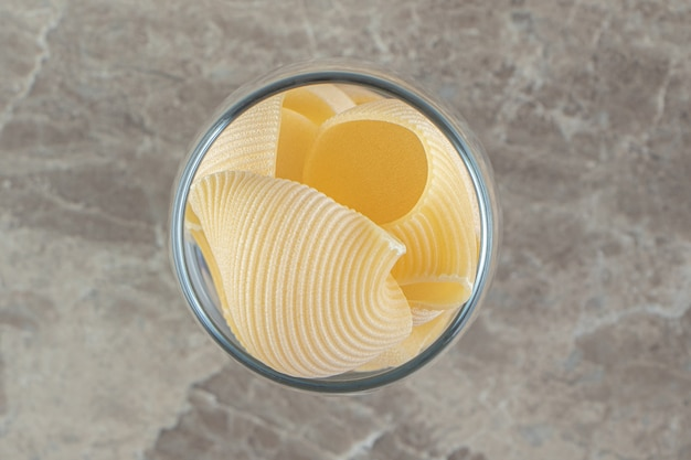 Ongekookte conchiglie pasta in lang glas.