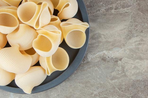 Ongekookte conchiglie pasta op zwarte bord.