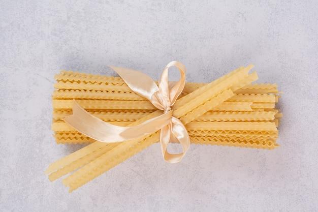 Ongekookte deegwaren die met lint op witte oppervlakte worden gebonden