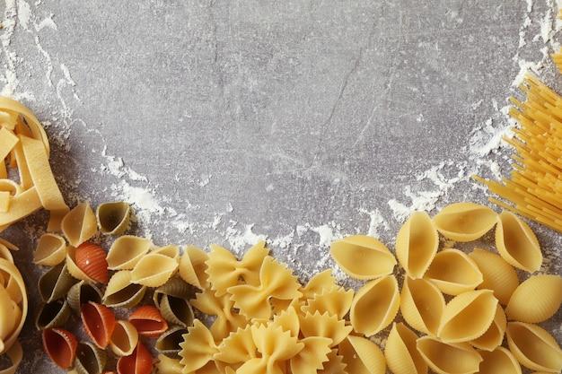 Ongekookte deegwaren en bloem op grijs gestructureerd oppervlak