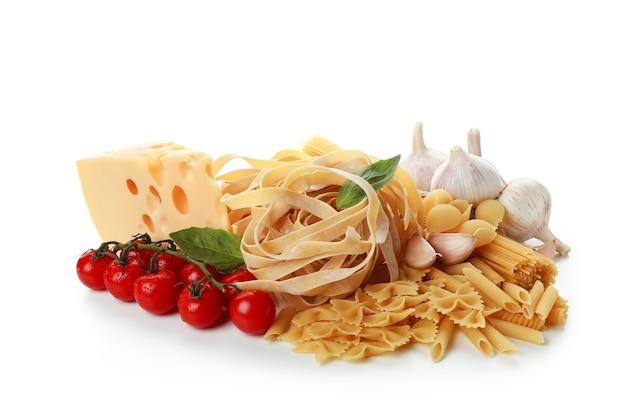 Ongekookte deegwaren en ingrediënten die op witte oppervlakte worden geïsoleerd