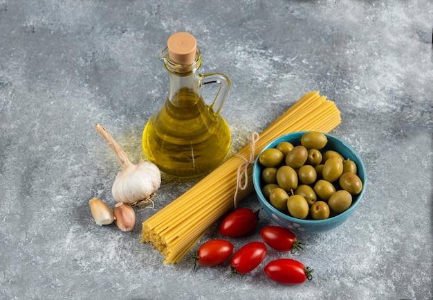 Ongekookte deegwaren, olie en verse groenten op steen.