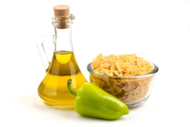 Ongekookte deegwaren, peper en een fles olie op wit.