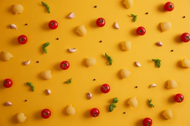 Ongekookte deegwaren, rode tomaten, basilicumbladeren en peperkorrels op gele achtergrond. ingrediënten voor het bereiden van heerlijke pasta. traditioneel italiaans eten of keuken. producten om te koken. bovenaanzicht
