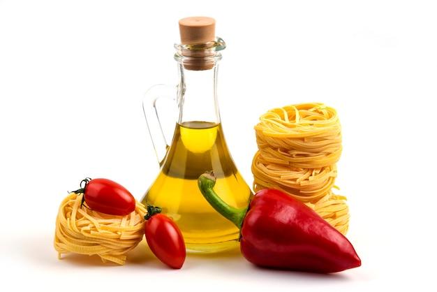 Ongekookte deegwarennesten, groenten en fles olie op wit.