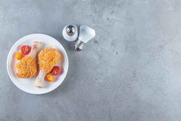 Ongekookte drumsticks op een bord naast zout, op de marmeren achtergrond.
