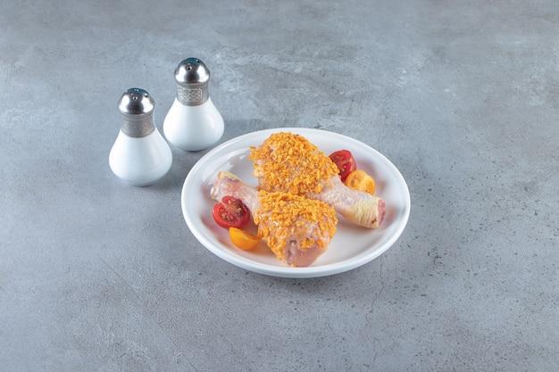 Ongekookte drumsticks op een bord naast zout, op het marmeren oppervlak.