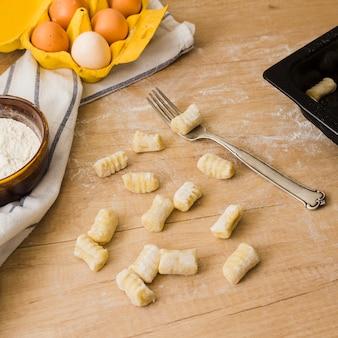 Ongekookte eigengemaakte aardappelgnocchi met vork over houten lijst met bloem en eieren