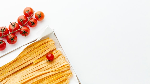 Ongekookte fettuccine en tomaten met exemplaarruimte