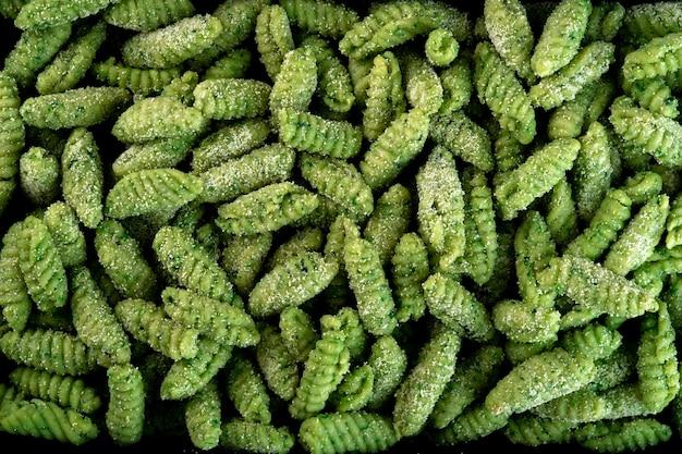 Ongekookte gnocchitextuur. italiaanse gekleurde pasta gnocchi close-up. voedsel achtergrond