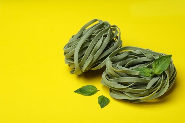 Ongekookte groene deegwaren en basilicum op geel