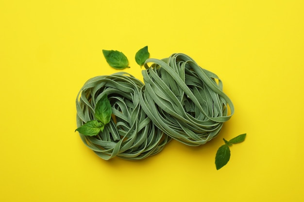 Ongekookte groene deegwaren en basilicum op gele oppervlakte