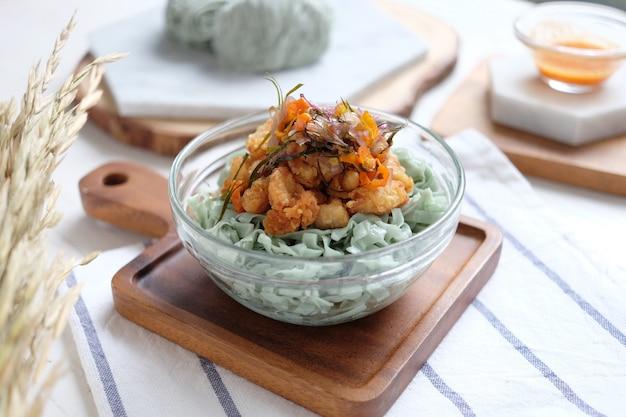 Ongekookte groene noedels met vlees en kipnugget op de kom