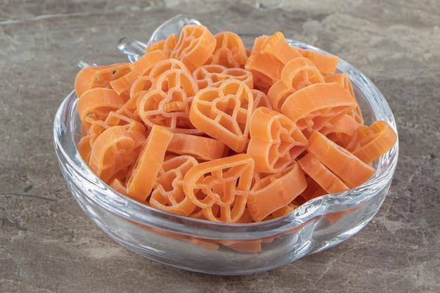 Ongekookte hartvormige pasta geplaatst in glazen kom