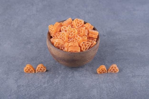 Ongekookte hartvormige pasta in houten kom.