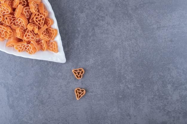 Ongekookte hartvormige pasta op bladvormige plaat.