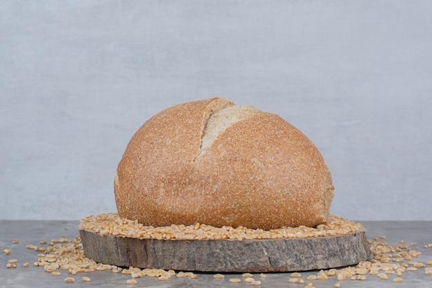 Ongekookte haverkorrels met brood op marmeren oppervlak