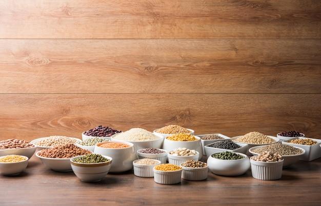 Ongekookte indiase peulvruchten, granen en zaden in witte kommen over houten oppervlak. selectieve focus