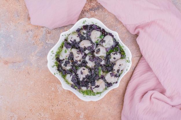 Ongekookte kaukasische khinkali met gehakte kruiden in een kom.