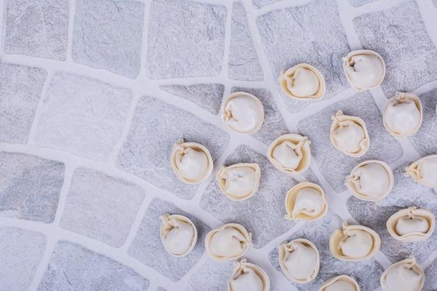 Ongekookte khinkali-vullingen op meel op de grond.