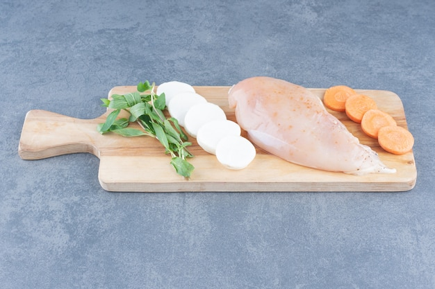 Ongekookte kipfilet met groenten op een houten bord.