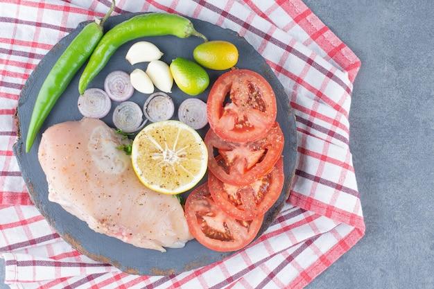 Ongekookte kipfilet op een houten bord met groenten.