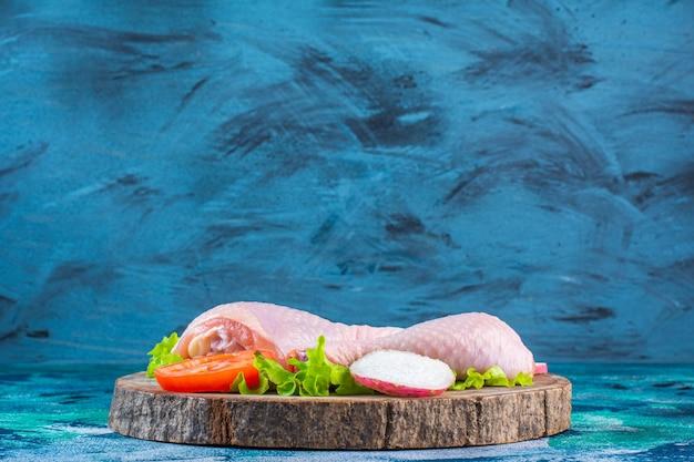 Ongekookte kippendrumstick naast tomaten, radijs op een bord