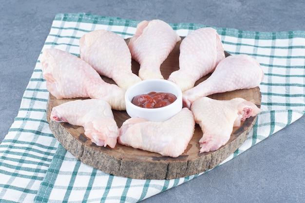 Ongekookte kippenpoten en vleugels op houten stuk.