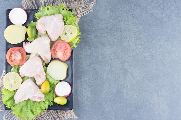 Ongekookte kippenvleugels en groenten op zwarte plaat.